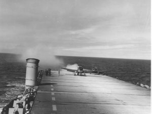 US Navy WWII plane landing on an aircraft carrier