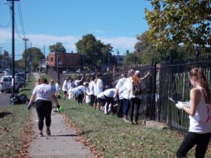 Volunteers working on cleaning up around a gate at Mount Moriah Cemetery